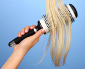 Blond curls brushing comb on color background — Stock Photo