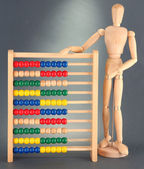 Bright toy abacus and wooden dummy, on grey background — Stock Photo