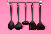 Black kitchen utensils on silver hooks, on pink background — Stock Photo