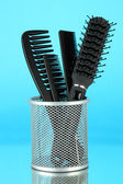 Iron basket with combs and hair brush, on color background — Stock Photo