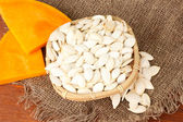Pumpkin seeds in wicker box, on wooden background — Stock Photo