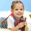 Cute little girl playing with multicolor pencils, on blue background — Stock Photo #19338721