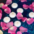 Rose petals and candles in water close-up — Stock Photo