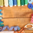 Stock Photo: Sewing accessories and fabric on wooden table close-up