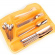 Orange plastic cutlery tray with checked silver cutlery and wooden spoons isolated on white - Stock Photo