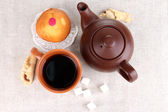 Top view of cup of tea and teapot on linen tablecloths — Stock Photo