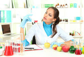 Young female scientist injecting GMO into apple in laboratory — Photo