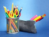 Caixa de lápis com equipamento escolar sobre fundo azul — Fotografia Stock