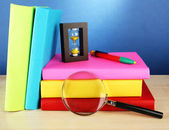 Color books with magnifying glass on table on blue background — Stock Photo