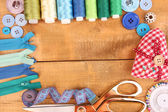 Sewing accessories and fabric on wooden table close-up — Stock Photo