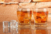 Glasses of whiskey and ice on brick wall background — Stock Photo