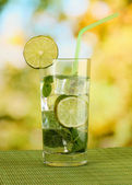 Glass of water with ice, mint and lime on table on bright background — Stock Photo
