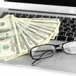 Money with glasses on laptop close-up — Stock Photo