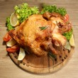 Whole roasted chicken with vegetables on plate, on wooden table — Foto de stock #19340901