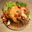 图库照片: Whole roasted chicken with vegetables on plate, on wooden table