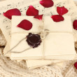 Stacks of old letters and music sheets with dried rose petals on soft scarf - Stok fotoğraf