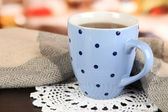 Cup of tea with scarf on table in room — ストック写真