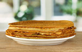 Sweet pancakes on plate on table in kitchen — Stock Photo