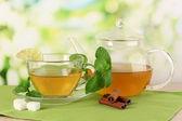 Filiżanka herbaty z mięty, wapno i cynamon na stole na jasnym tle — Zdjęcie stockowe