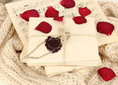 Stacks of old letters and music sheets with dried rose petals on soft scarf — Stock Photo