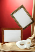 White mask, empty frames and golden silk fabric, on red background — Stock Photo