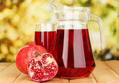 Full glass and jug of pomegranate juice and pomegranate on wooden table outdoor — Stock Photo