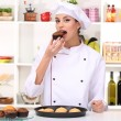 Young woman chef with cakes on dripping pan in kitchen — Stock Photo