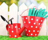 Gardening tools on green grass on wooden fence background — 图库照片