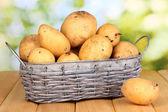 Maduras batatas na cesta na mesa de madeira no fundo natural — Fotografia Stock