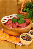 Raw beef meat with herbs and spices on wooden table on brown background — Stock Photo