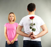 Loving man holding red rose for his woman on grey background — Stock Photo