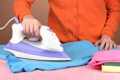 Young woman ironing her clothes, on brown background — Stock Photo
