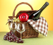 Picnic basket and bottle of wine on cloth on yellow background — Stock Photo