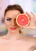 Beautiful young woman with bright make-up, holding grapefruit, on bright background — Stock Photo