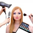 Stock Photo: Beautiful young woman and hands with eyes shadows, brush and hairdryer, isolated on white