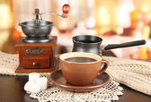 Cup of coffee with scarf and coffee mill on table in room — Stock Photo