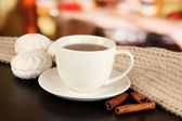Cup of tea with scarf on table in room — Stockfoto