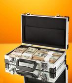 Kufr s 100 dolarové bankovky na oranžovém pozadí — Stock fotografie