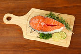 Fresh salmon steak on cutting board, on wooden background — Stock Photo
