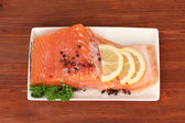 Fresh salmon fillet with herbals and lemon slices on plate, on wooden background — Stock Photo