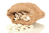 Pumpkin seeds in sack, isolated on white — Stock Photo