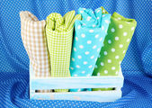 Color mottled fabrics in basket on blue fabric background — Stock Photo