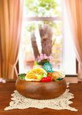 Secchi arance, palle di vimini e altre decorazioni casa in ciotola di legno, su sfondo luminoso — Foto Stock