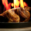 Foto Stock: Whole roasted chicken on plate, on flame background
