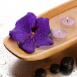 Spa stones and wooden bowl with candles and purple flower, on wet background - Foto Stock