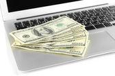 Money on laptop isolated on white — Stock Photo