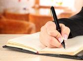 Hand schreibt am notebook, auf hellem hintergrund — Stockfoto