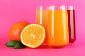 Glasses of juise with leafs and fruits on pink background — Stock Photo