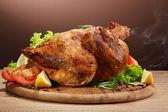 Geheel gebraden kip met groenten, op houten tafel, op bruine achtergrond — Stockfoto