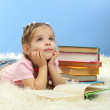 Cute little girl with colorful books, on blue background — Stockfoto